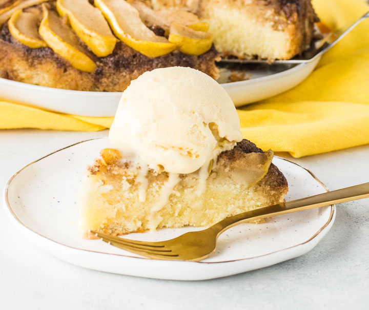 slice of pear cake on a plate topped with a scoop of vanilla ice cream