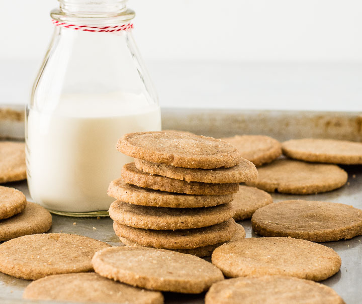 stack of Dutch windmill cookies (biscoff cookies) on a cookie tray in front of a bottle of milk