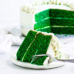 slice of green velvet cake on a plate with the rest of the cake in the background