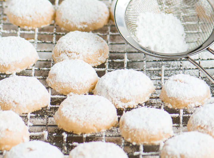 melting moments cookies on a wire rack with a sifter of powdered sugar next to them