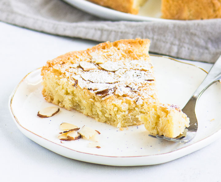 slice of almond cake on a plate with a fork taking a bite out of it