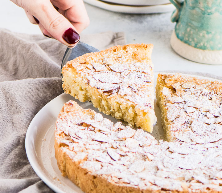 hand lifting a slice of Swedish almond cake off of a cake plate