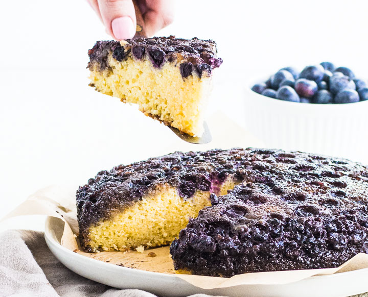 blueberry cake on a cake plate with a hand lifting a slice up