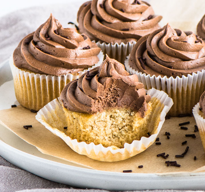 peanut butter cupcakes on a cake plate with chocolate sprinkles next to them