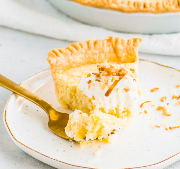 slice of coconut custard pie on a plate with a fork taking a bite out of it