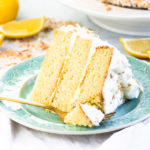 slice of lemon coconut cake on a plate with a fork taking a bite out of it