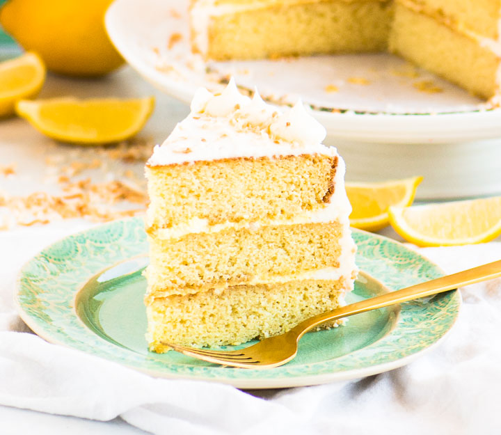 slice of coconut lemon cake on a plate with the cake on a cake stand behind it