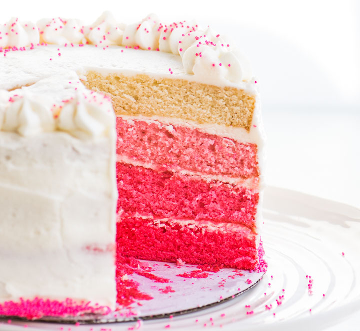 sliced pink ombré cake on a cake stand
