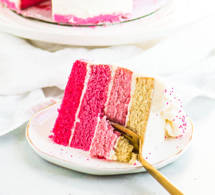 slice of pink ombre cake on a plate with a fork taking a bite out of it
