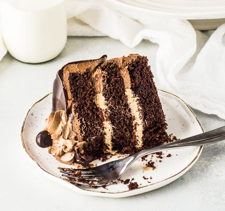 slice of cake on a plate with a fork and a bottle of milk behind it