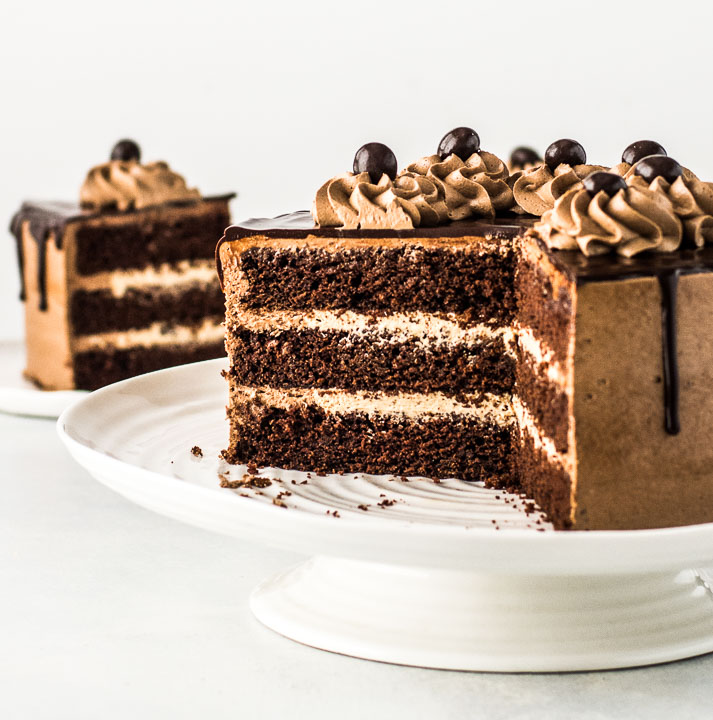 sliced cake on a cake stand in front of a slice of cake on a plate