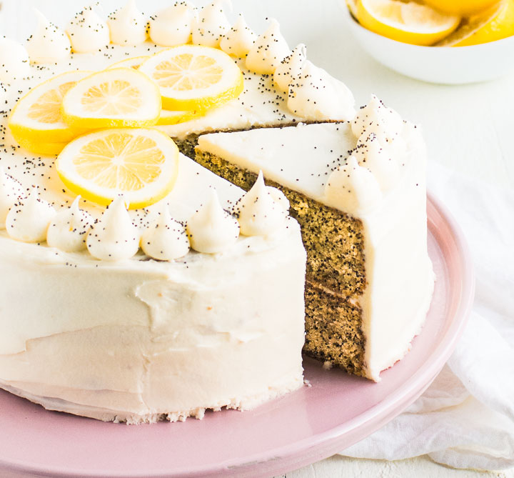 lemon poppy seed cake on a cake stand, sliced so you can see the inside of the cake
