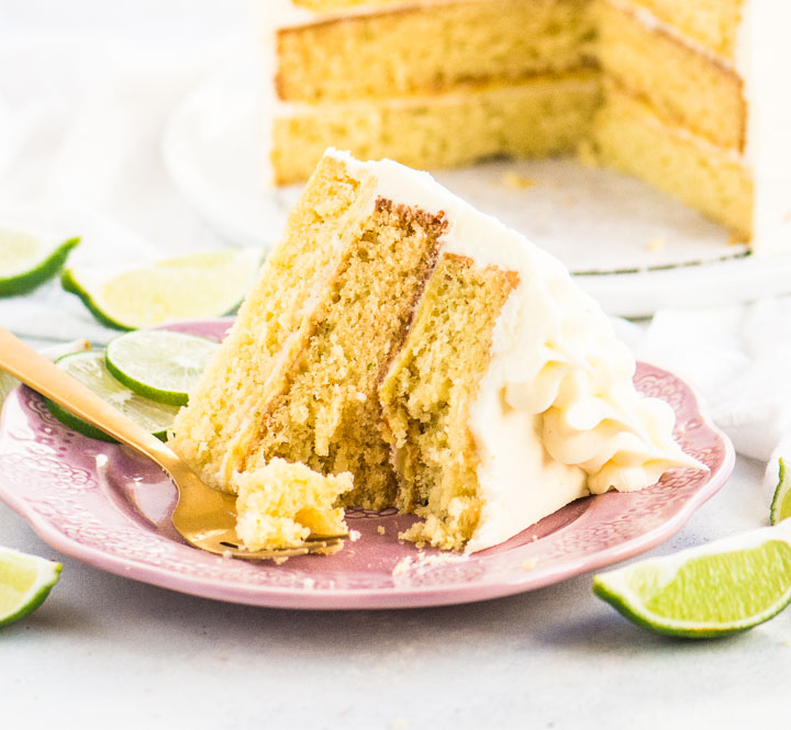 slice of lime cake on a plate with a fork taking a bite out of it and the rest of the cake behind it