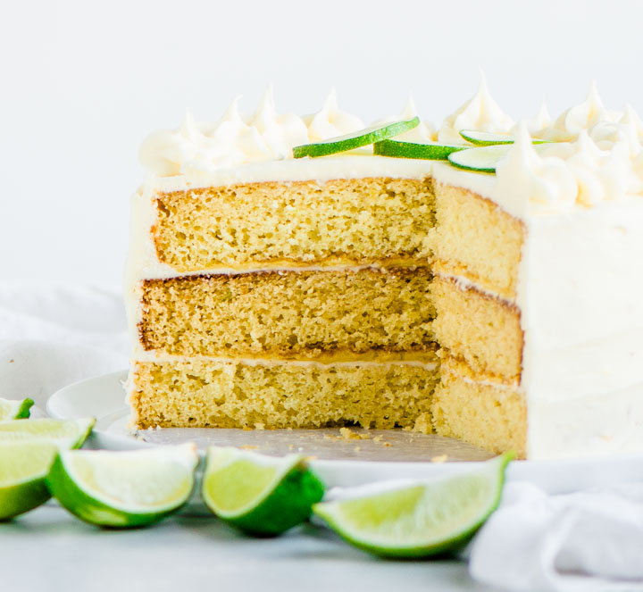 sliced cake on a cake stand with sliced limes in front of it