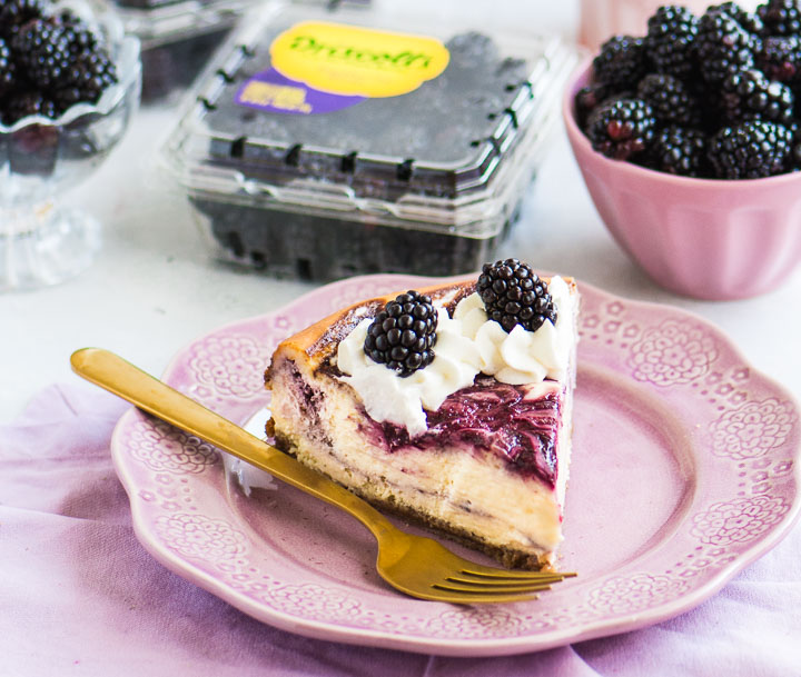 slice of cheesecake on a plate with a fork next to it and packages of berries behind it