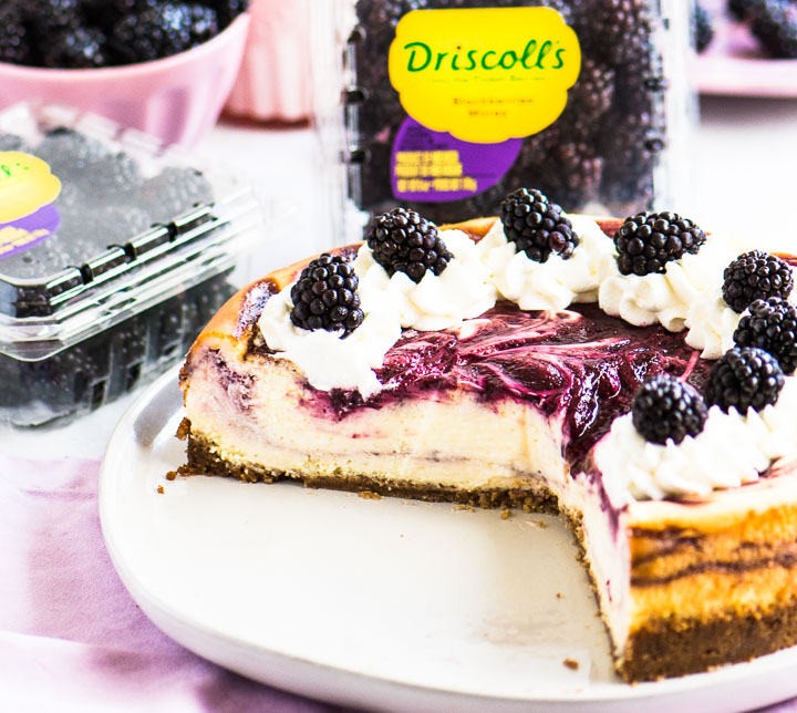 sliced cheesecake on a cake plate with packages of blackberries behind it