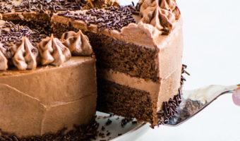 cake on a cake plate with a cake server lifting a slice up