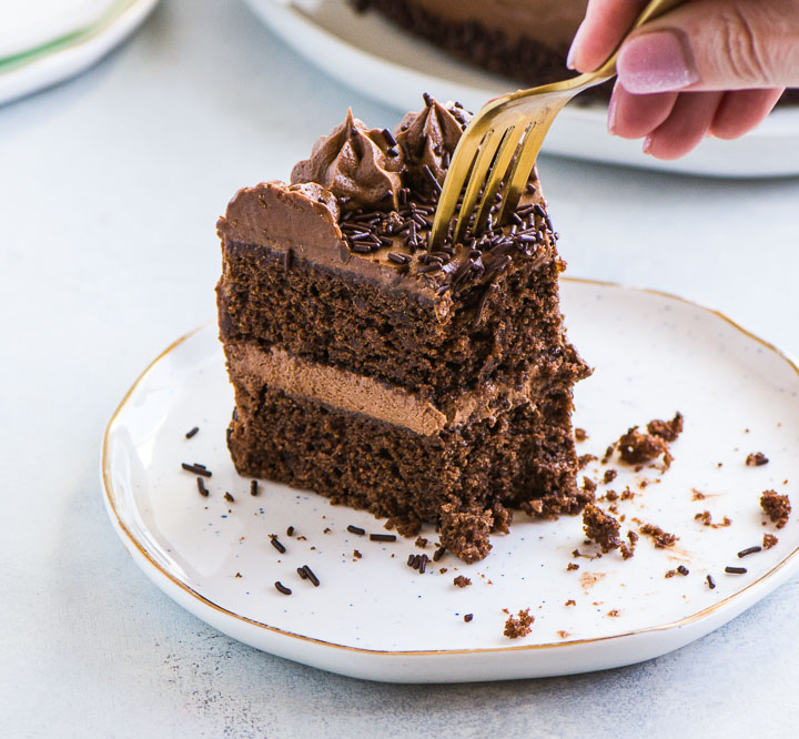 hand reaching with a fork to take a bite out of a slice of chocolate buttermilk cake
