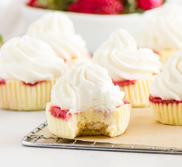 strawberry cheesecake cupcake on a wire rack with more cheesecakes and a bowl of strawberries in the background