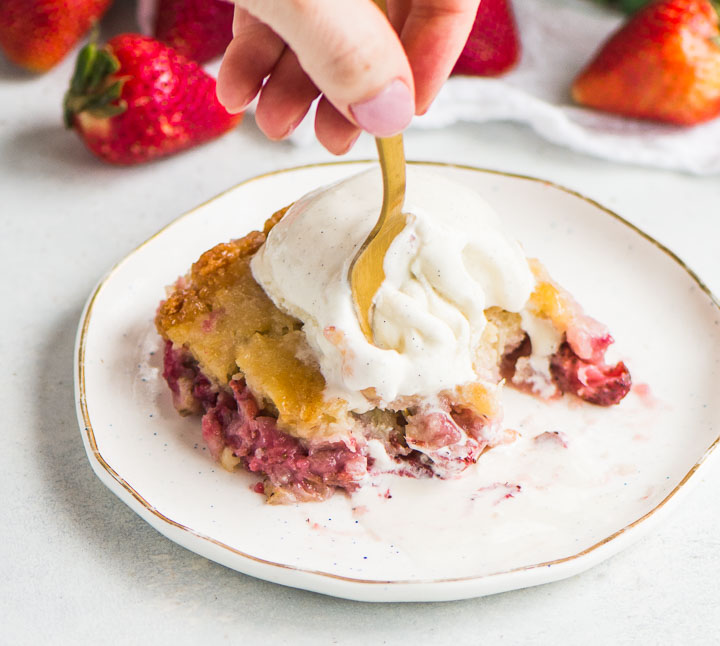 slice of cake with ice cream on top and a hand taking a bite with a fork
