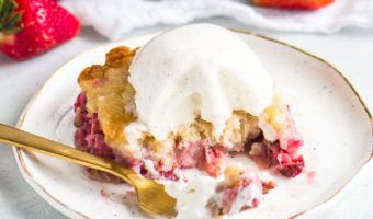 strawberry cake on a plate with a fork and strawberries in the background