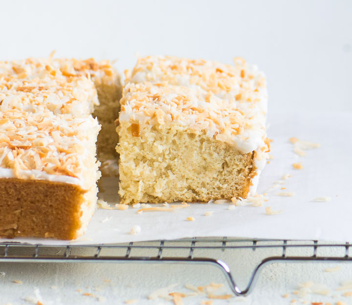 sliced coconut cake on top of a wire rack with a piece of parchment underneath