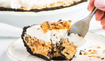 slice of Butterfinger pie on a plate with a hand holding a fork taking a bite out of the pie and the rest of the pie behind it