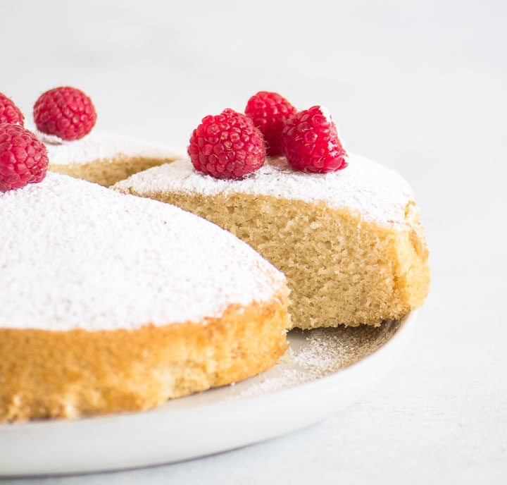 sliced cake on a cake plate with powdered sugar and raspberries on top