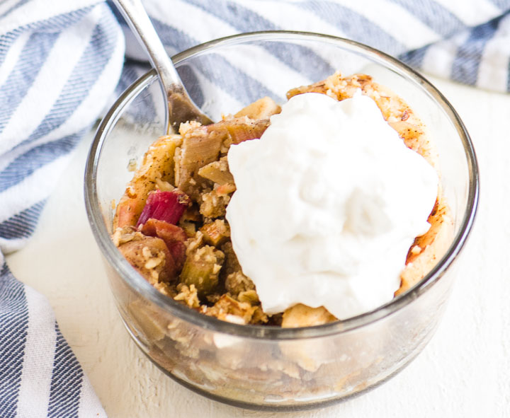 scoop of apple rhubarb crisp in a bowl with a striped towel behind it