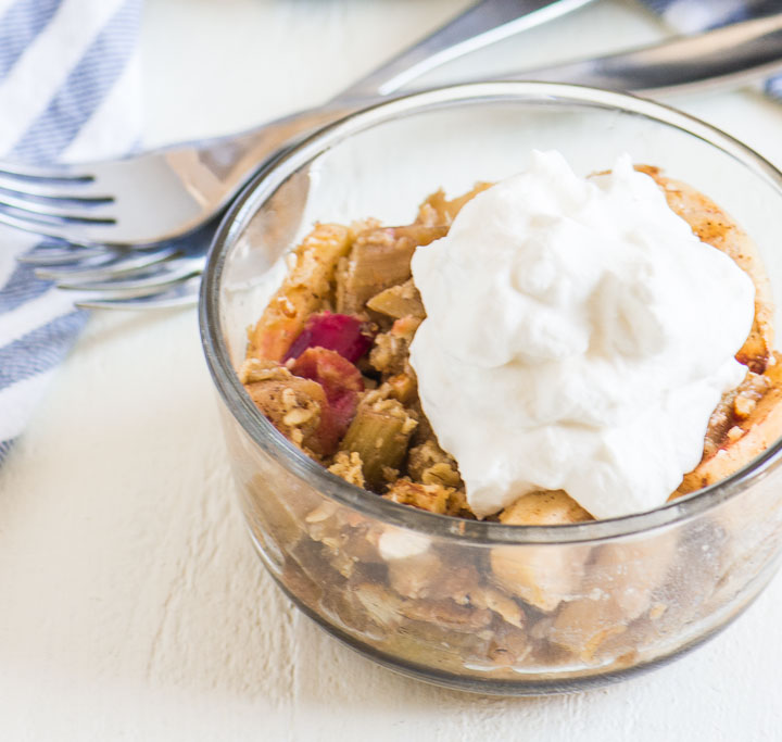 scoop of rhubarb apple crisp in a bowl with two forks and a striped towel behind it