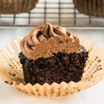 mocha cupcake sliced in half to show the texture of the chocolate cake with a wire rack in the background