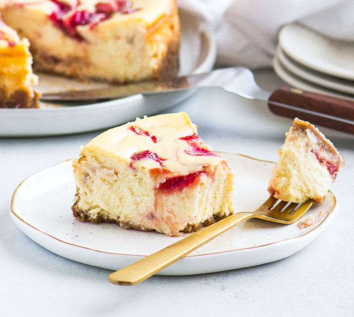 slice of rhubarb cheesecake on a plate with a stack of plates and the rest of the cheesecake in the background
