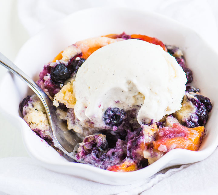 fork digging into a bowl of cobbler with vanilla ice cream on top