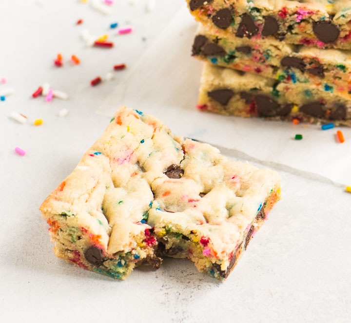 cookie bar with a bite out of it in front of a stack of bars with sprinkles next to it