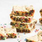 stack of cookie bars on a square of parchment paper with sprinkles around it and a bar with a bite taken out of it in front
