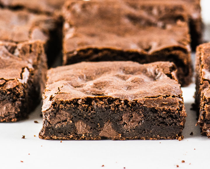 close up photo of sliced brownie with other brownies behind it