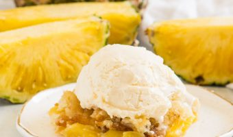 cobbler on a plate with vanilla ice cream on top and fresh pineapple behind it