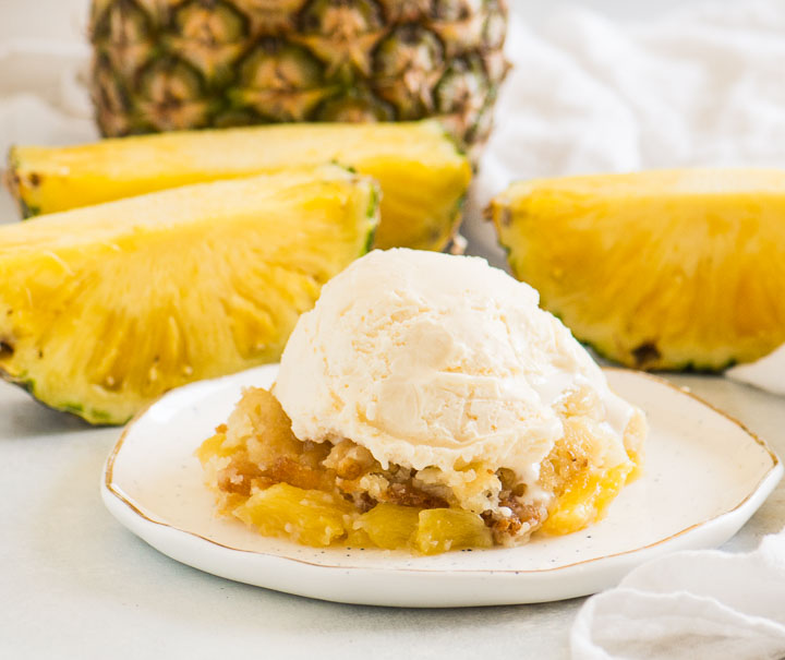 scoop of cobbler on a plate with ice cream on top and a slices of pineapple behind it