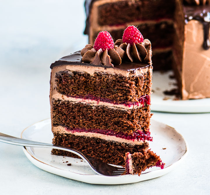 slice of cake in front of the rest of the chocolate raspberry cake