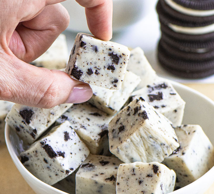 hand picking a piece of fudge up out of a bowl of fudge with Oreos in the background