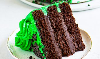 slice of peppermint chocolate cake on a plate in front of the rest of the cake