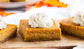 three pumpkin bars topped with whipped cream on a serving board in front of a plate of more bars