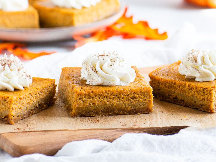 three pumpkin pie bars on a serving board in front of a plate of more bars