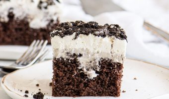 slice of Oreo poke cake on a plate with a fork and another cake slice in the background