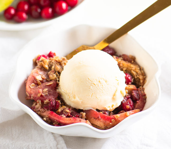 cranberry apple crisp in a bowl with a scoop of ice cream