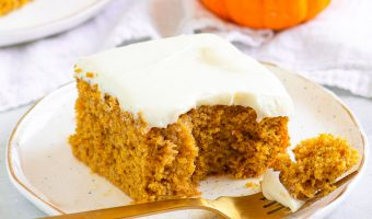 slice of cake on a plate with a fork and a small pumpkin and another slice of cake in the background