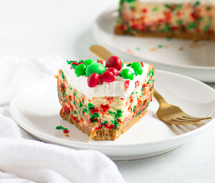 slice of Christmas cheesecake on a plate with a fork next to it and the rest of the cake in the background