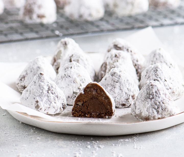 cookies on a plate with one sliced open to show the chocolate kiss in the middle