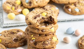 stack of four cookies in front of a wire rack with cookies on top and more cookies and mini eggs arranged around them