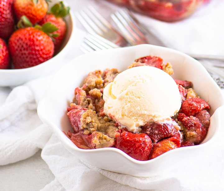 bowl of strawberry crumble topped with ice cream with a bowl of fresh strawberries in the background
